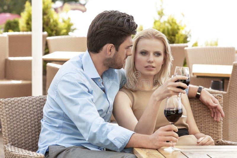 Potomstwa dobierają się opowiadać podczas gdy mieć czerwone wino przy plenerową restauracją fotografia stock