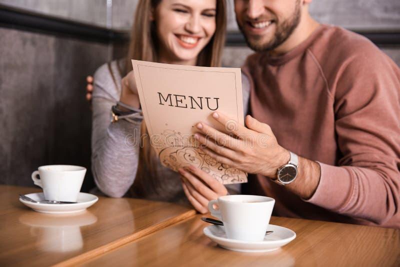Potomstwa dobierają się patrzeć przez menu w restauracji zdjęcia royalty free