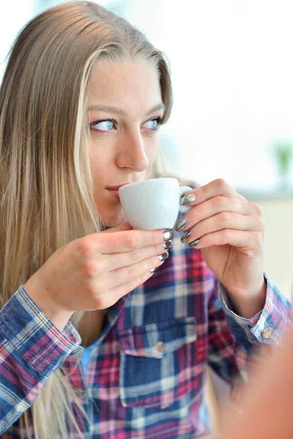 Potomstwa dobierają się pić kawę w kawiarni przed szklaną fasadą - mężczyzna i kobieta - obrazy stock