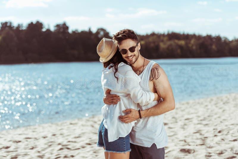 Potomstwa dobierają się przytulenie podczas gdy stojący przy piaskowatą plażą fotografia royalty free
