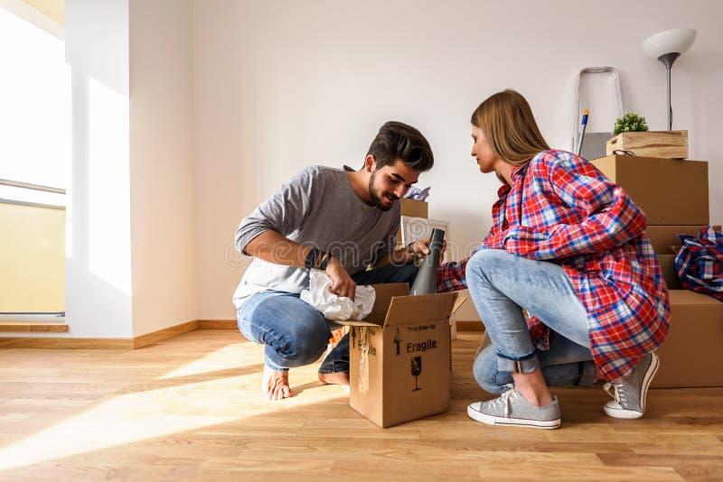 Potomstwa dobierają się właśnie poruszonego w nowego pustego mieszkania odpakowanie, czyścić i - przeniesienie fotografia royalty free