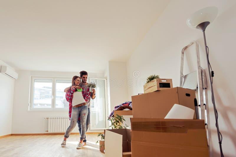Potomstwa dobierają się właśnie poruszonego w nowego pustego mieszkania odpakowanie, czyścić i - przeniesienie zdjęcia stock