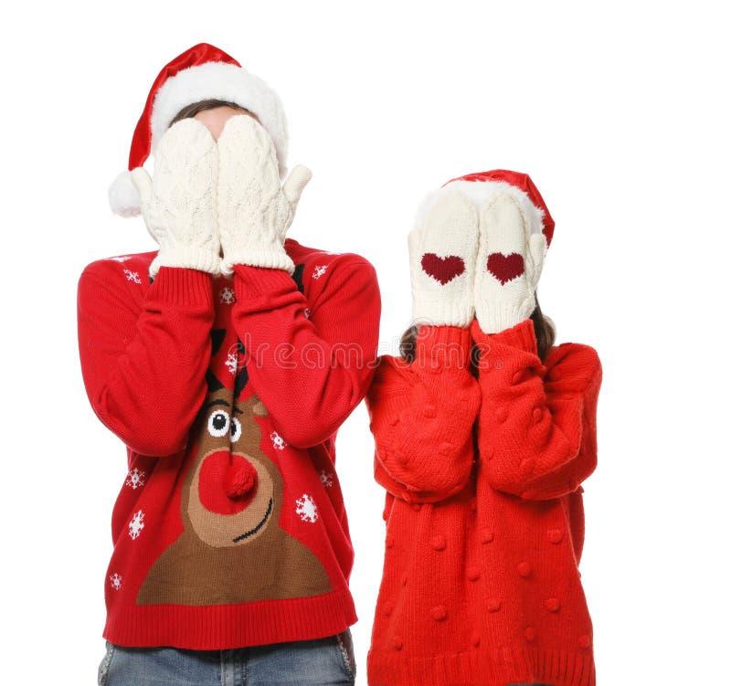 Potomstwa dobierają się w Bożenarodzeniowych pulowerach i kapeluszach na bielu obrazy stock