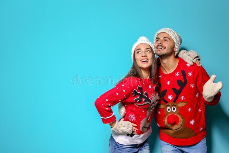 Potomstwa dobierają się w Bożenarodzeniowych pulowerach i trykotowych kapeluszach na koloru tle zdjęcia royalty free