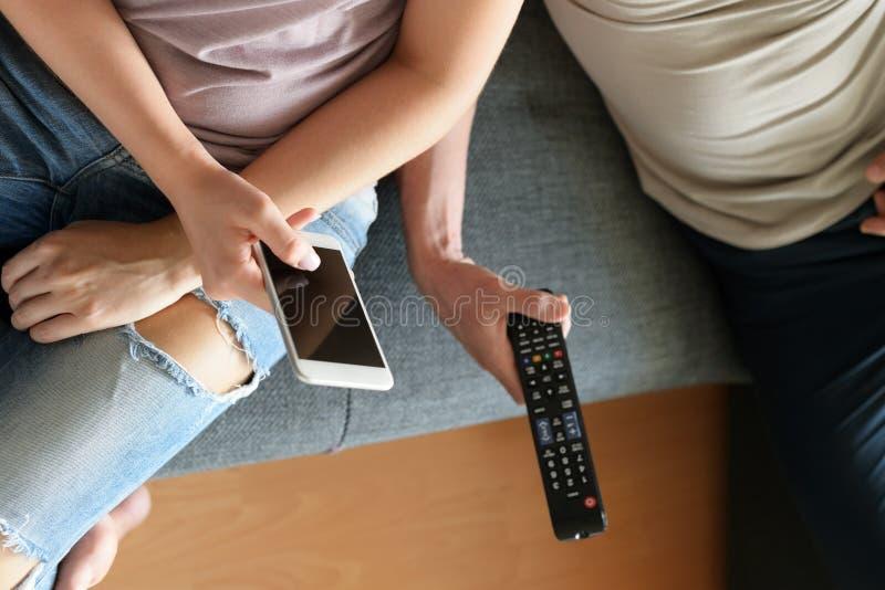 Potomstwa dobierają się w domu, oglądający telewizję i texting fotografia stock