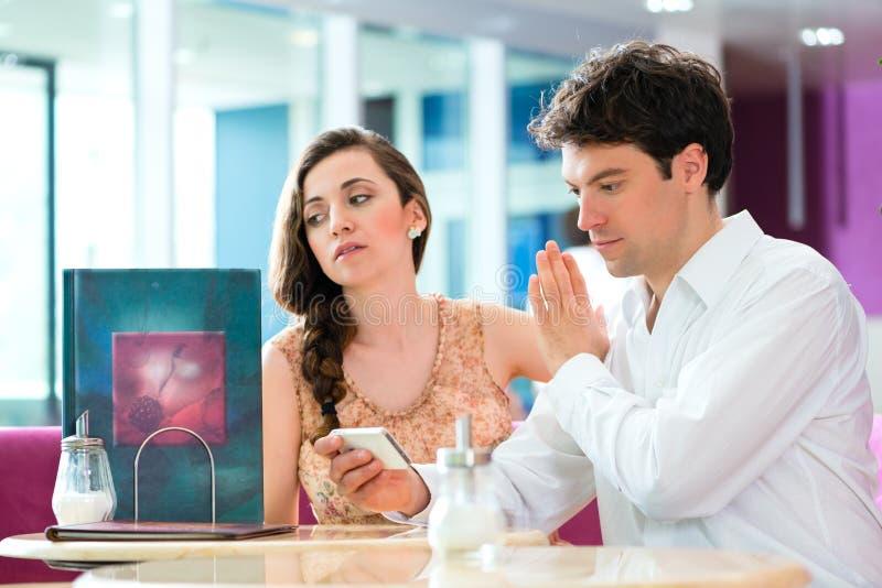 Potomstwa dobierają się w kawiarni no oddziała wzajemnie ale na telefonie zdjęcia royalty free