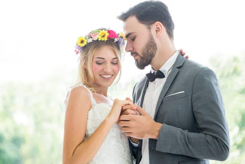 potomstwa dobierają się w miłości państwa młodzi mienia Ślubnej ręce wpólnie i patrzejący each innego całowanie w parku Nowożeńcy zdjęcia royalty free