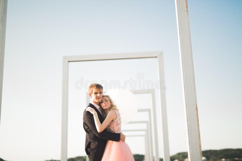 Potomstwa dobierają się w miłości pozuje na dachu z perfect miasto widoku mienia przytuleniem i rękami piękny zachód słońca fotografia stock