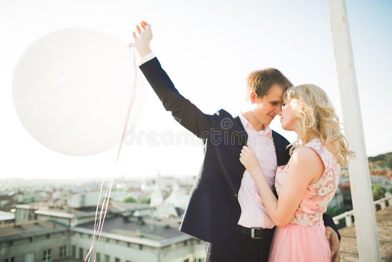Potomstwa dobierają się w miłości pozuje na dachu z perfect miasto widoku mienia przytuleniem i rękami piękny zachód słońca zdjęcie stock