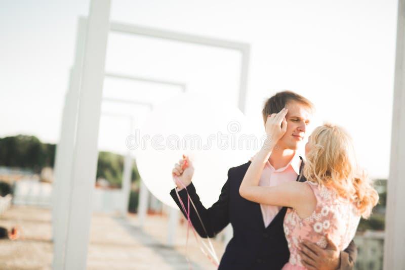 Potomstwa dobierają się w miłości pozuje na dachu z perfect miasto widoku mienia przytuleniem i rękami piękny zachód słońca fotografia royalty free