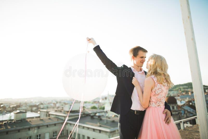 Potomstwa dobierają się w miłości pozuje na dachu z perfect miasto widoku mienia przytuleniem i rękami piękny zachód słońca obrazy stock