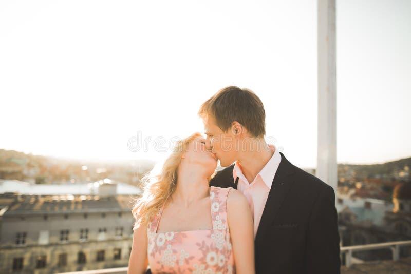 Potomstwa dobierają się w miłości pozuje na dachu z perfect miasto widoku mienia przytuleniem i rękami piękny zachód słońca obraz royalty free