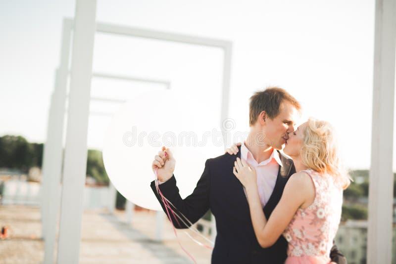 Potomstwa dobierają się w miłości pozuje na dachu z perfect miasto widoku mienia przytuleniem i rękami piękny zachód słońca zdjęcie royalty free