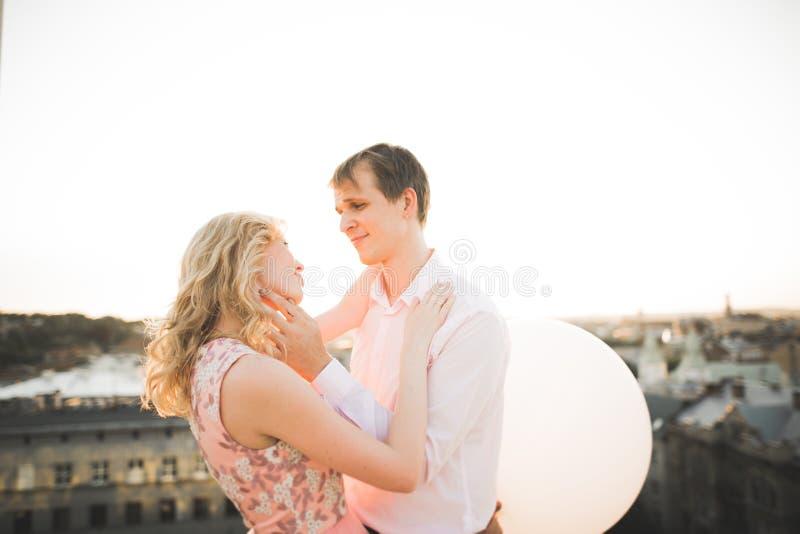 Potomstwa dobierają się w miłości pozuje na dachu z perfect miasto widoku mienia przytuleniem i rękami piękny zachód słońca obraz stock