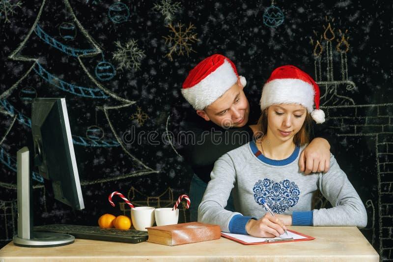 Potomstwa dobierają się w Santa kapeluszu pisze liście Święty Mikołaj fotografia royalty free