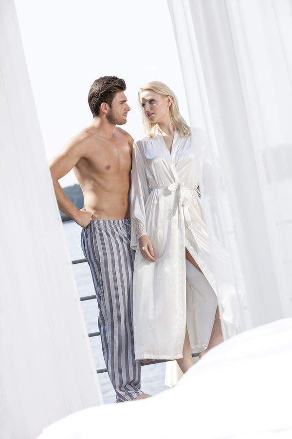 Potomstwa dobierają się w sleepwear patrzeje each inny na hotelowym balkonie fotografia royalty free