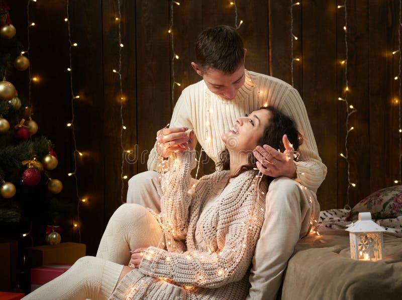 Potomstwa dobierają się wpólnie w bożonarodzeniowe światła i dekoraci ubierających w, białym, jedlinowym drzewie na ciemnym drewn fotografia royalty free