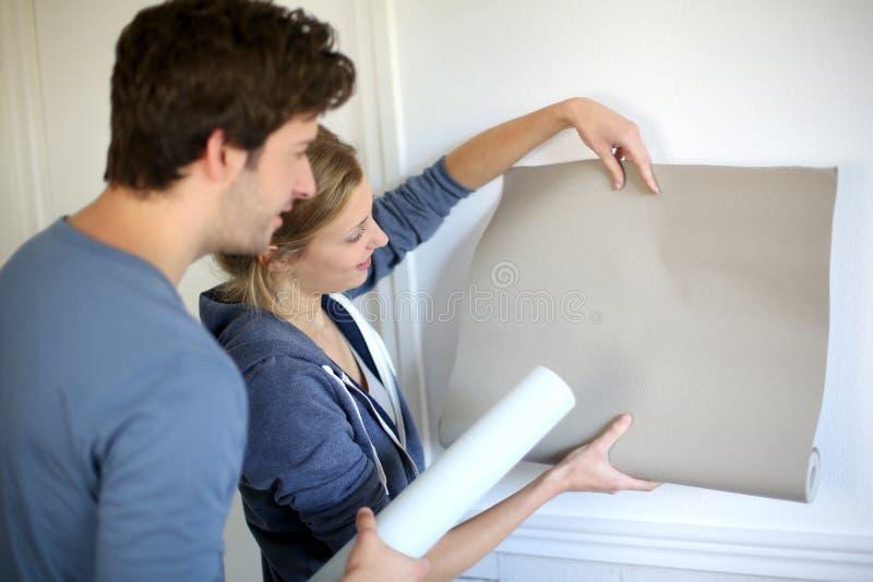 Potomstwa dobierają się wybierać tapety dla ich nowego mieszkania fotografia stock
