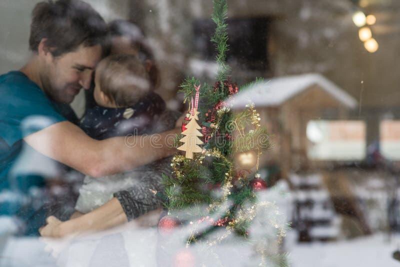 Potomstwa dobierają się z dziecko pozycją obok dekorujących boże narodzenia zdjęcie stock