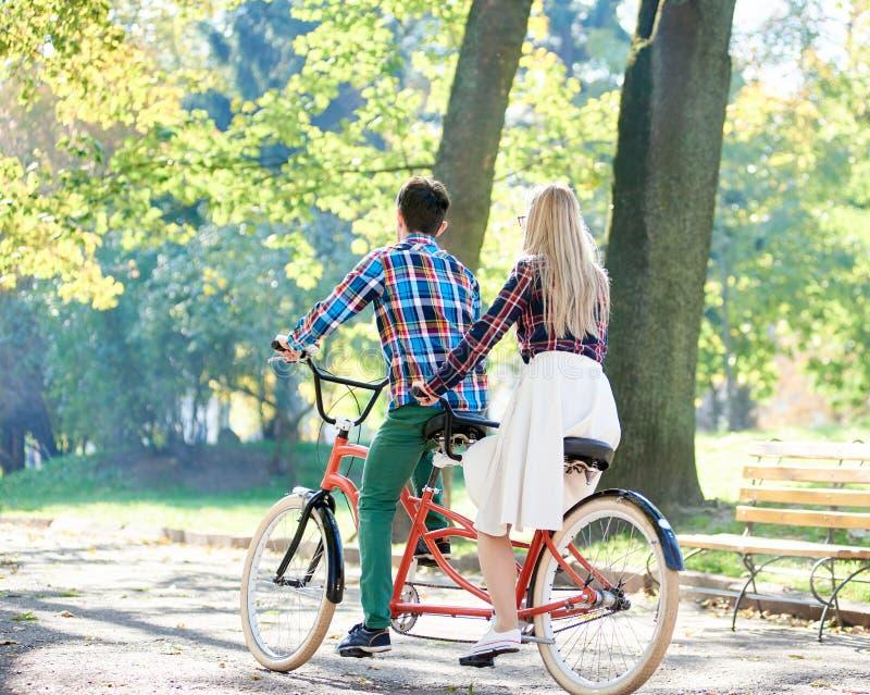 Potomstwa dobieraj? si?, przystojny m??czyzna i atrakcyjna kobieta na tandemowym rowerze w pogodnym lato parku, lesie lub zdjęcia royalty free