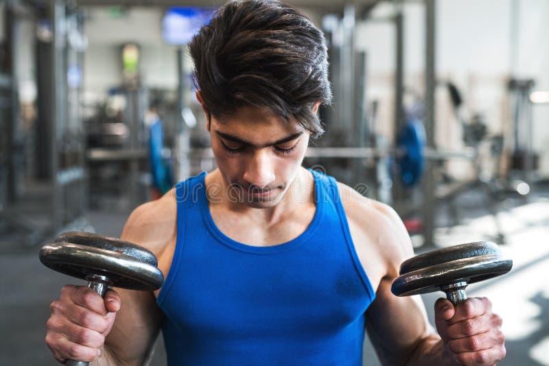 Potomstwa dostosowywali latynoskiego mężczyzna ćwiczy w gym z dumbbells fotografia royalty free