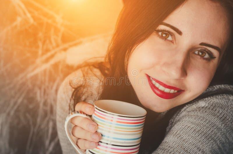 Potomstwa dosyć uśmiecha się dziewczyny utrzymują filiżankę napój w ciepłym pulowerze zdjęcie royalty free
