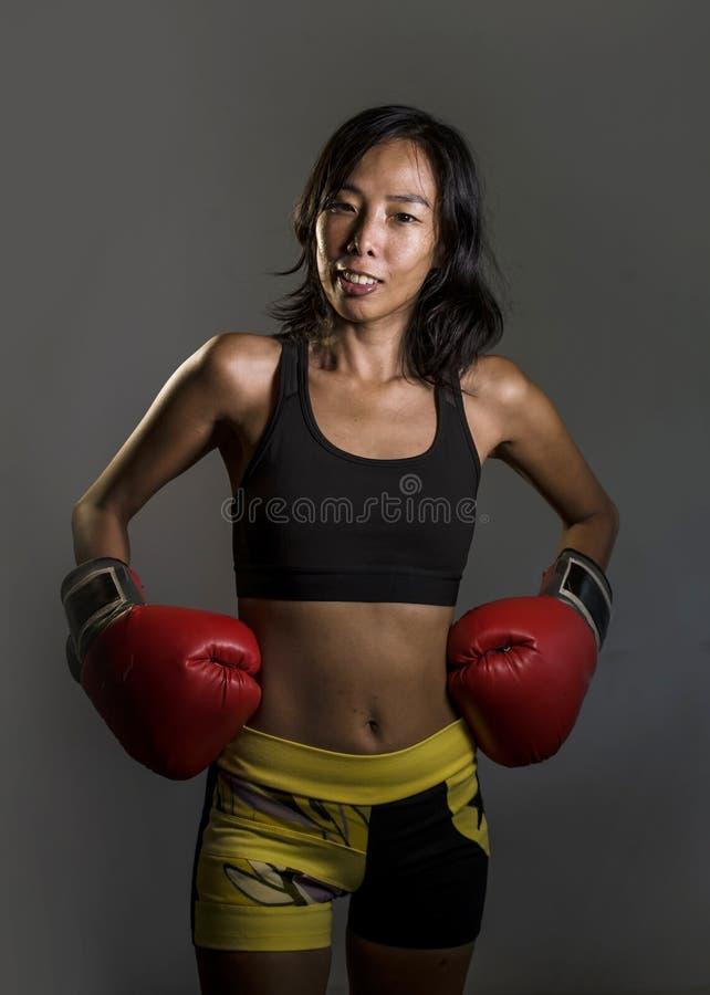 Potomstwa dysponowani i zdrowa Azjatycka Chińska kobieta z przepoconym sportowym ciałem w sprawności fizycznych rękawiczek pozowa zdjęcia stock