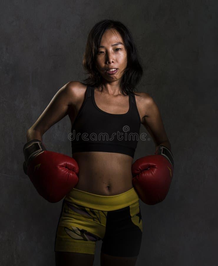 Potomstwa dysponowani i zdrowa Azjatycka Chińska kobieta z przepoconym sportowym ciałem w sprawności fizycznych rękawiczek pozowa zdjęcie stock