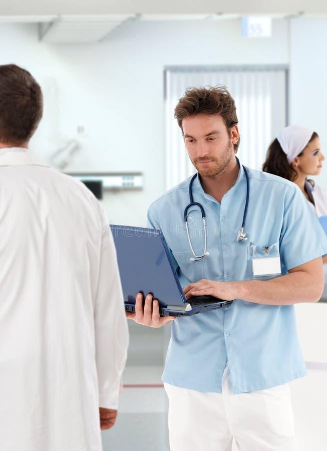 Potomstwa fabrykują działanie z laptopem w szpitalu fotografia stock