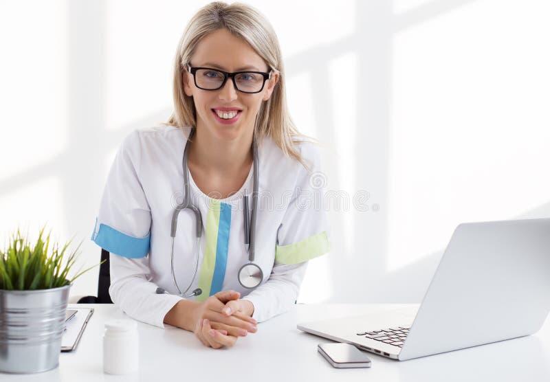 Potomstwa fabrykują obsiadanie przy biurkiem w jej biurze w klinice zdjęcia royalty free