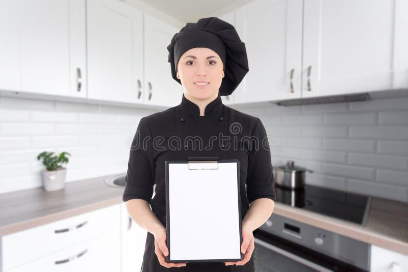 Potomstwa gotują kobiety w czerń jednolitym pokazuje pustym schowku fotografia stock