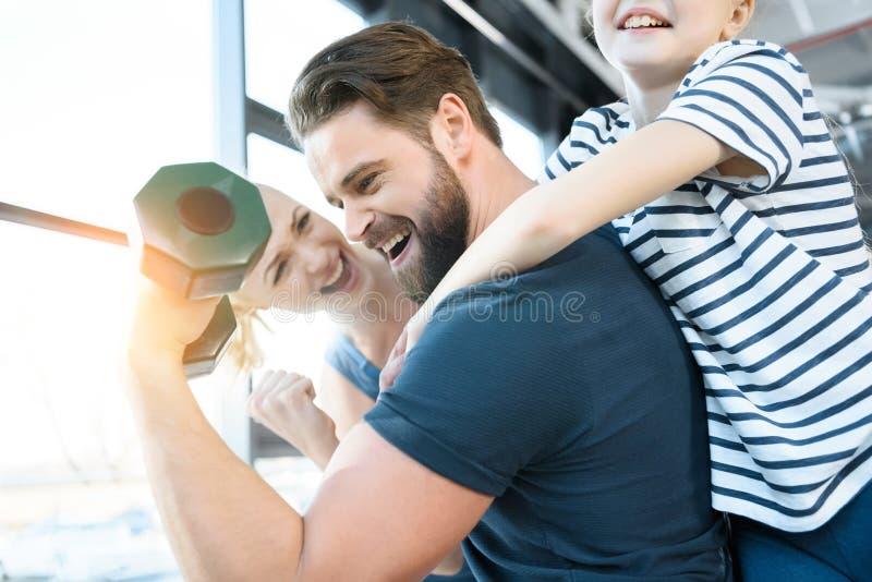 Potomstwa i dziewczyna faceta przyglądający trening z dumbbell obraz stock
