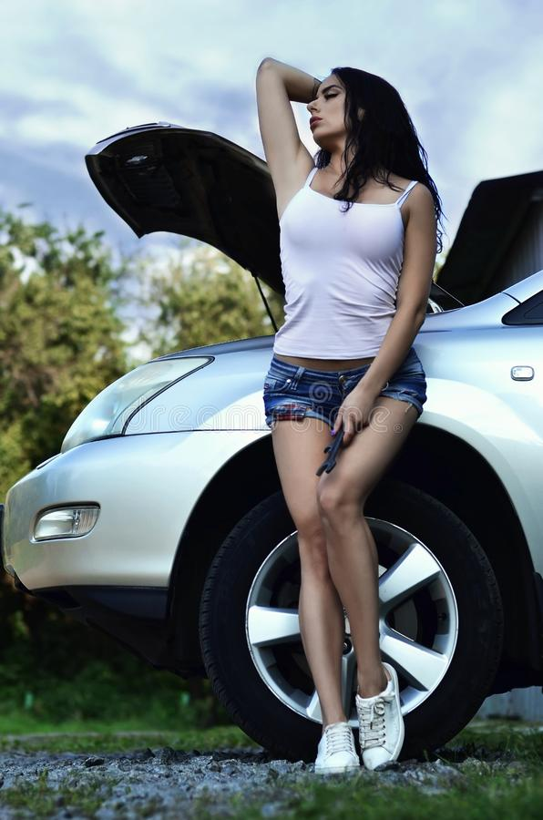 Potomstwa i dziewczyna z spanner blisko do srebnego samochodu z o obraz stock