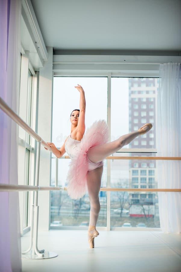 Potomstwa i niesamowicie piękna balerina są pozujący i tanczący w biały pracowniany pełnym światło zdjęcia stock