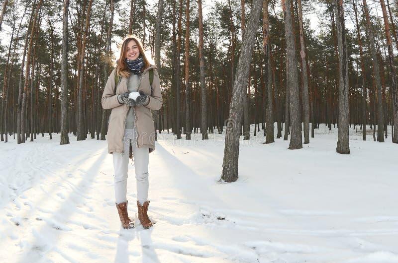 Potomstwa i radosna Kaukaska dziewczyna w brown żakiecie trzymają snowball w śnieżystym lesie w zimie Fisheye fotografia obraz royalty free