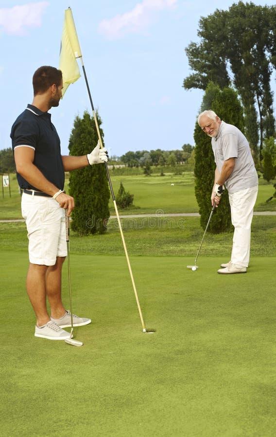 Potomstwa i stary człowiek grać w golfa wpólnie obrazy stock