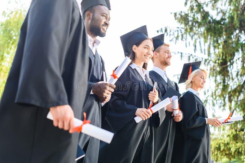 potomstwa kończyli studia uczni w przylądkach i kapeluszy trzymać zdjęcie royalty free