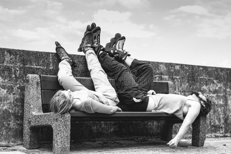 Potomstwa męczący ludzie przyjaciół relaksuje na ławce zdjęcia royalty free
