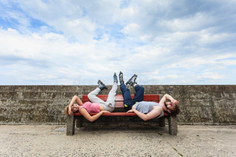 Potomstwa męczący ludzie przyjaciół relaksuje na ławce fotografia stock