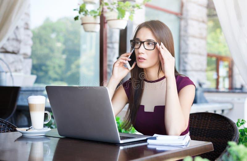 Potomstwa męczyli bizneswomanu pracuje na laptopie i opowiada na telefonie fotografia stock