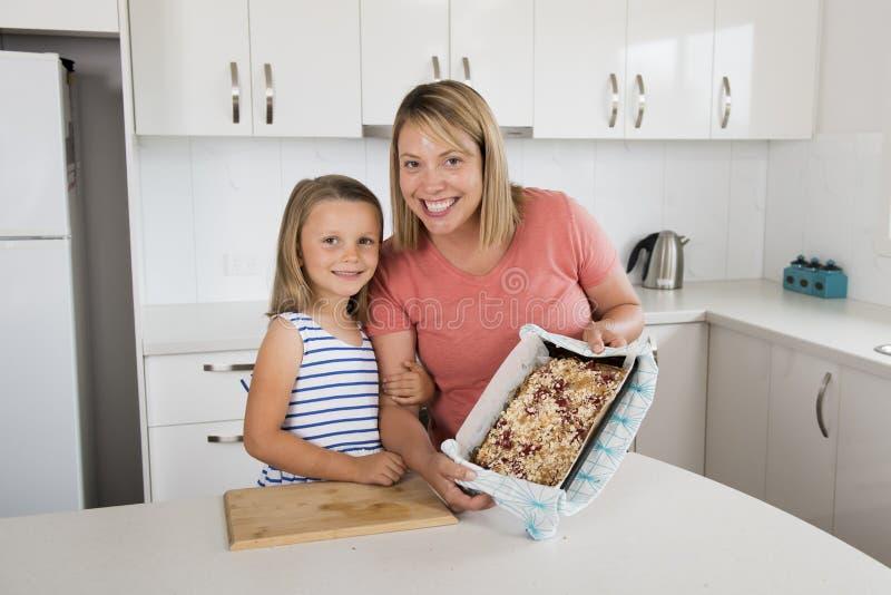 Potomstwa macierzyści i jej słodka piękna 7 lat córka pokazuje dumnego truskawka tort po piec wpólnie w domu kuchennego smil zdjęcia stock