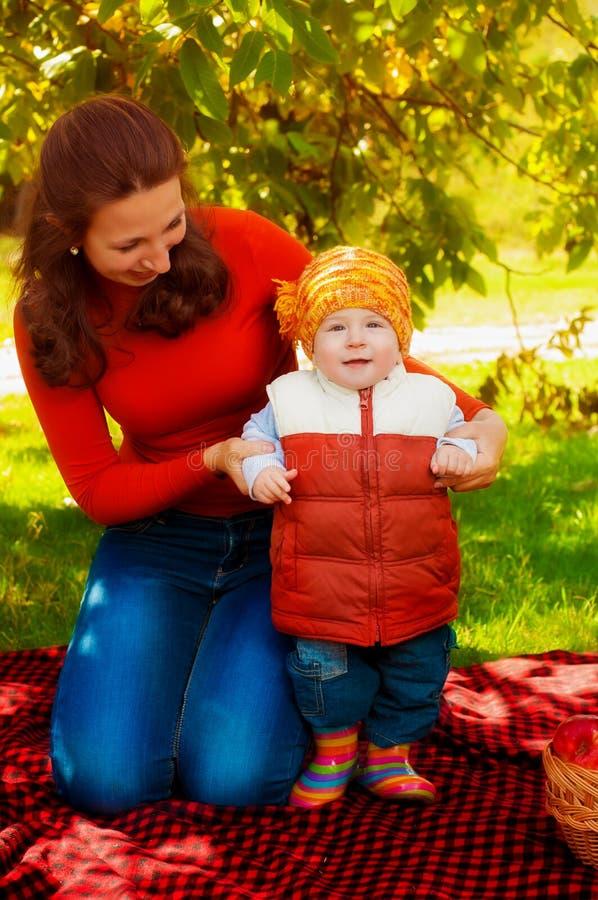 Potomstwa macierzyści i mały syn w jesieni z koszem jabłka fotografia stock