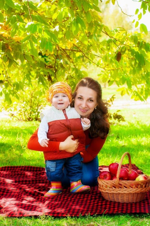 Potomstwa macierzyści i mały syn w jesieni z koszem jabłka obrazy royalty free