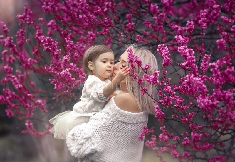 Potomstwa matkują z uroczą córką w parku z okwitnięcia drzewem Szczęśliwa matka i dziecko obrazy stock