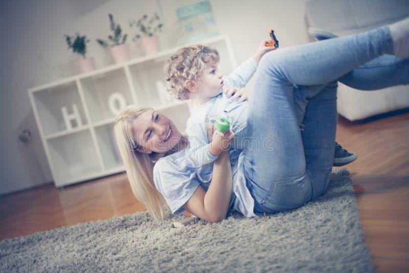 Potomstwa matkują bawić się w żywym pokoju z jej chłopiec obrazy royalty free