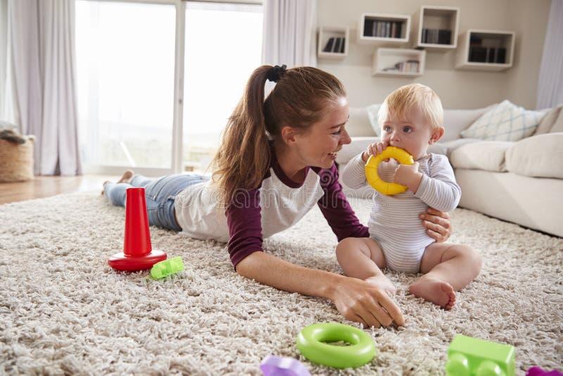 Potomstwa matkują bawić się z berbecia synem na podłoga w domu obrazy royalty free