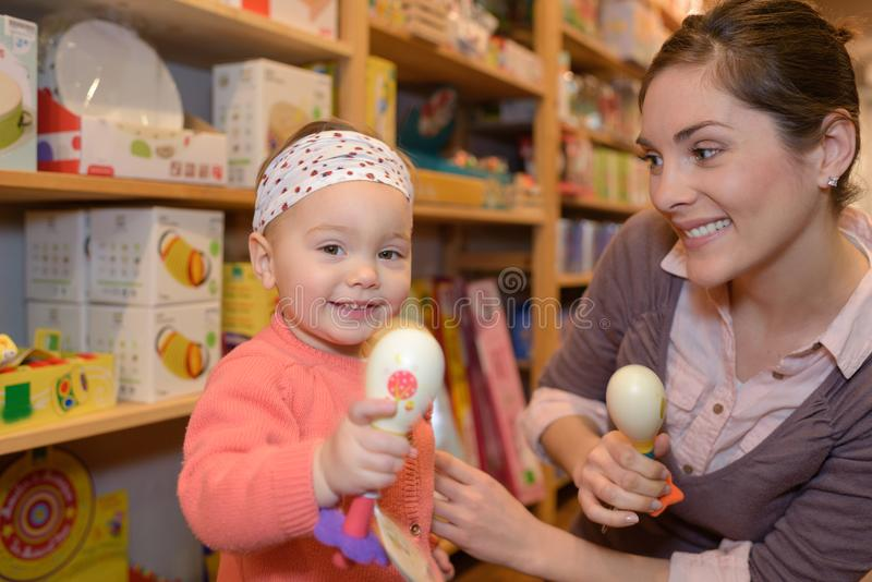 Potomstwa matkują córka zakupy przy zabawkarskim sklepem obraz stock