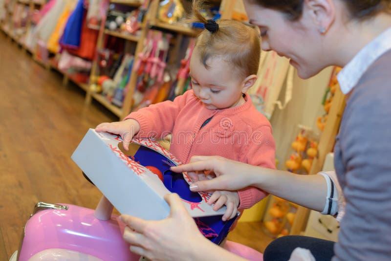 Potomstwa matkują córka zakupy przy zabawkarskim sklepem zdjęcie royalty free