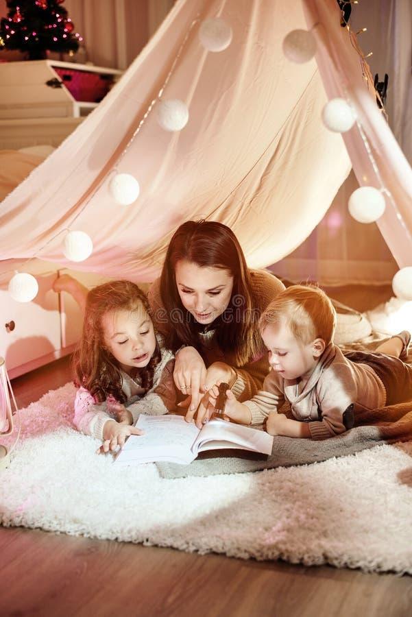Potomstwa matkują czytać powieści z ona dzieciaków fotografia royalty free