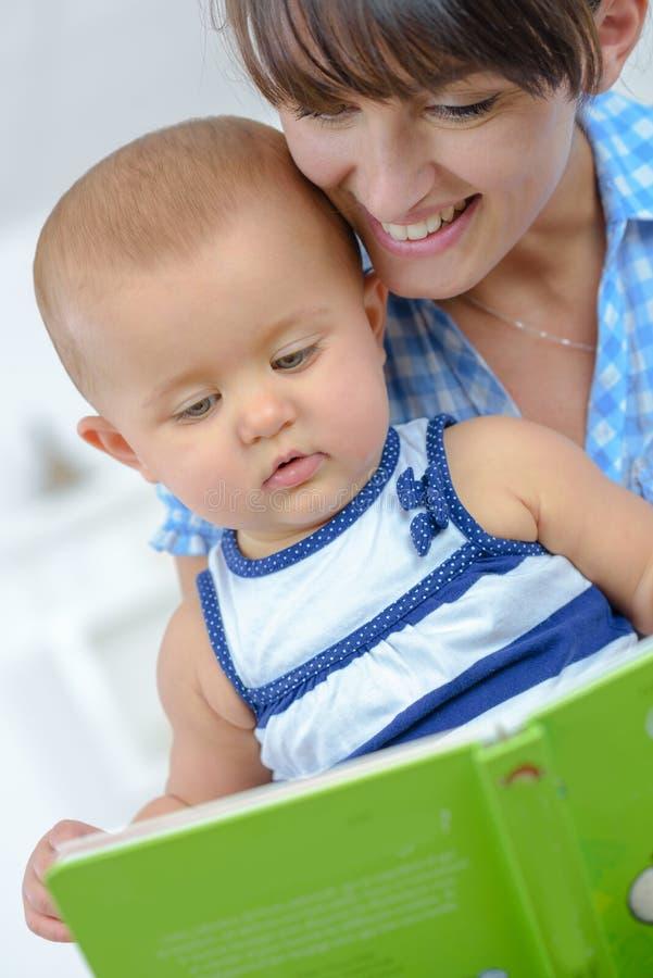Potomstwa matkują czytelniczą książkę dziecko zdjęcia stock